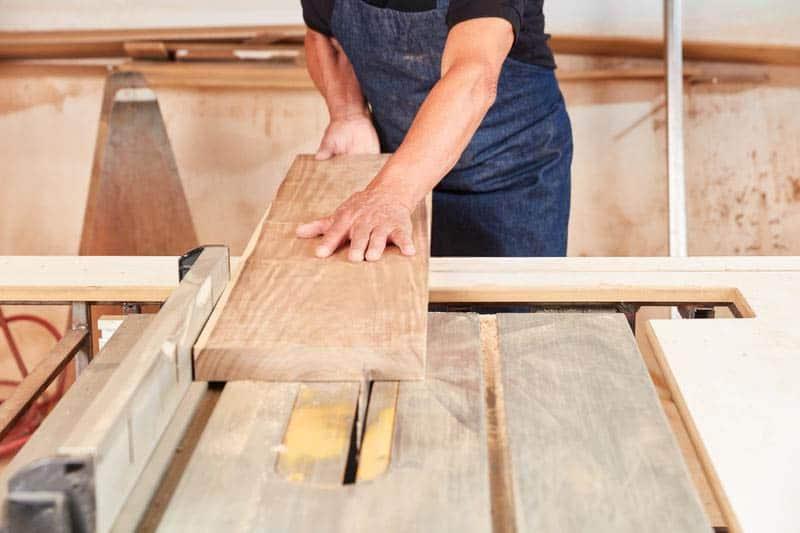 Carpenter saws a wood board.
