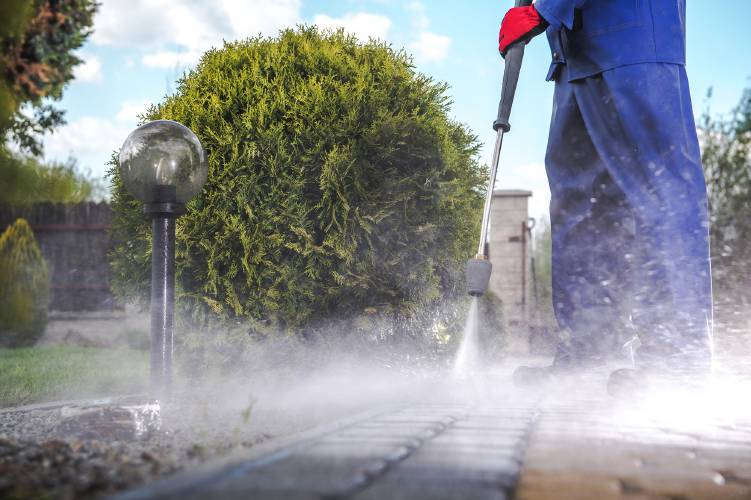 A man using a pressure washer to clean a brick path.