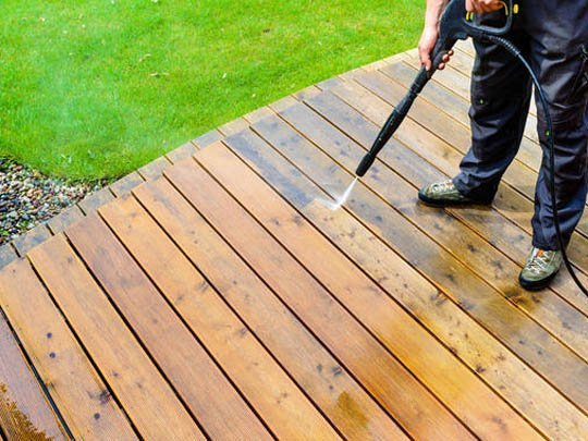 A wooden deck being pressure washed. The cleaned portion of the deck is much brighter in color than the part waiting to be cleaned showing how dramatic a difference removing the dirt has made.