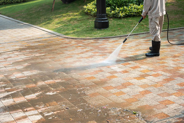 A driveway being cleaned by a pressure washer showing how effectively it removes dirt and grime from stone.