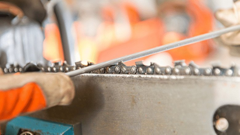 A close up shot of a round file being used to sharpen the cutters on a chain.