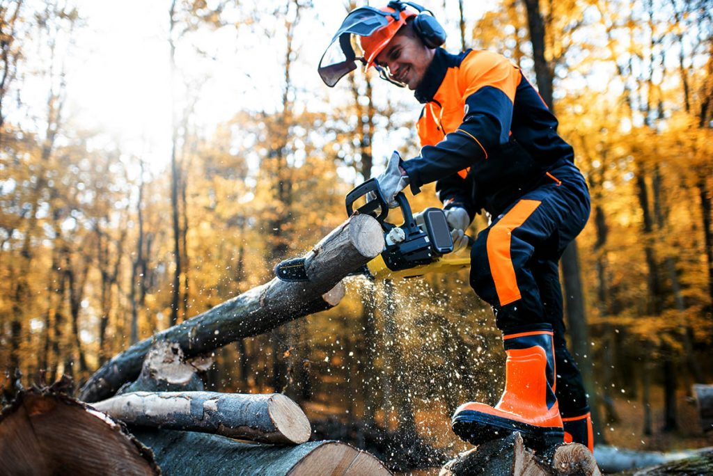 A man using a chainsaw while wearing protective gear including chainsaw chaps