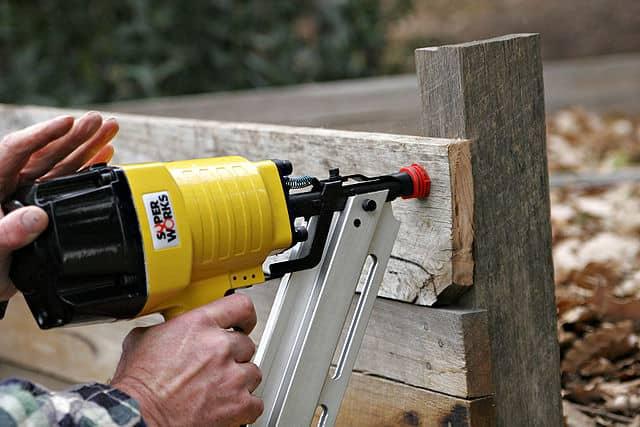 Using a nail gun to attach a plank to a wood beam.