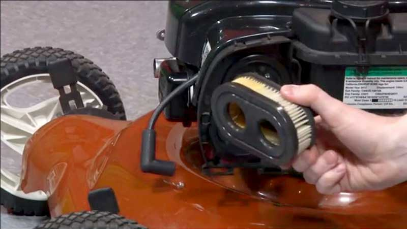 Someone changing the air filter on an orange lawn mower