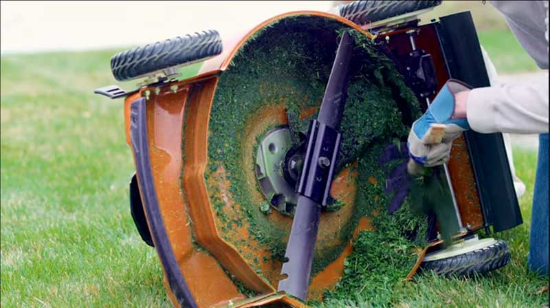 Someone cleaning the underside of an orange mower, an important part of lawn mower maintenance.
